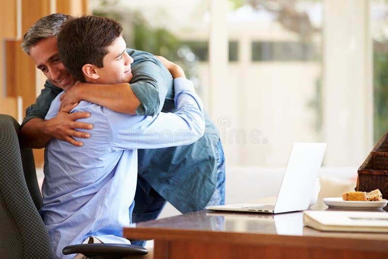 Fader And Teenage Son som har en kram arkivfoton