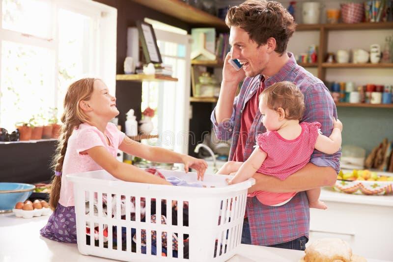 Fader Using Mobile Phone, som han sorterar tvätterit med barn arkivbilder