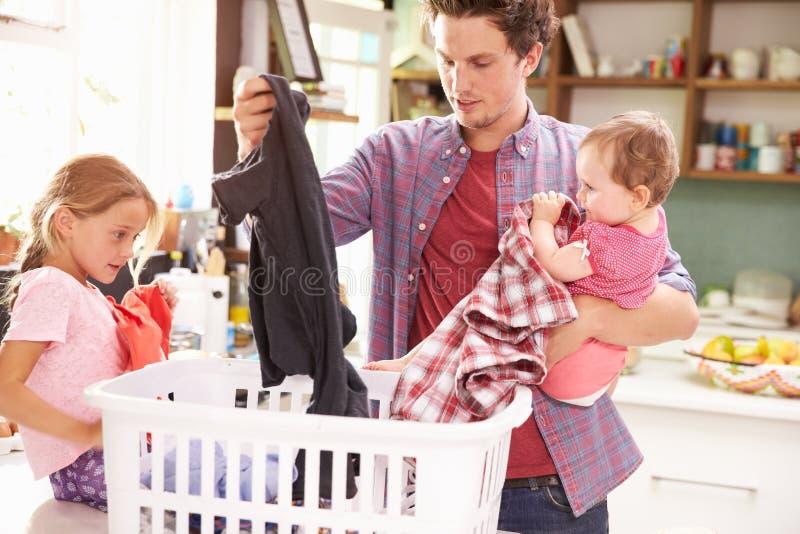FaderAnd Children Sorting tvätteri i kök royaltyfri foto