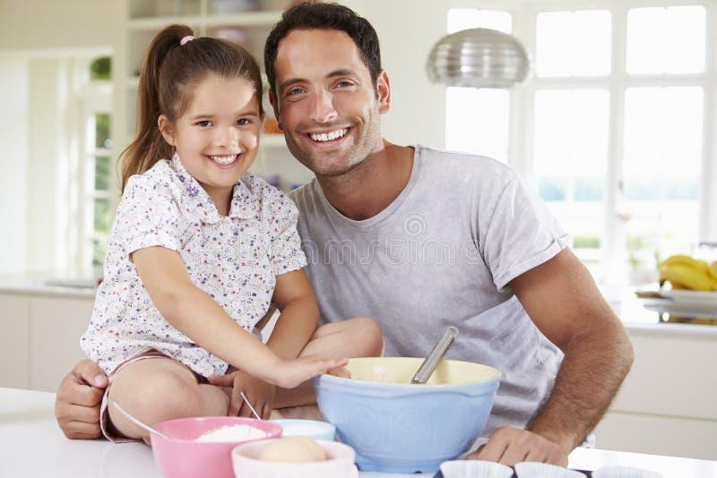 FaderAnd Daughter Baking kaka i kök royaltyfria foton
