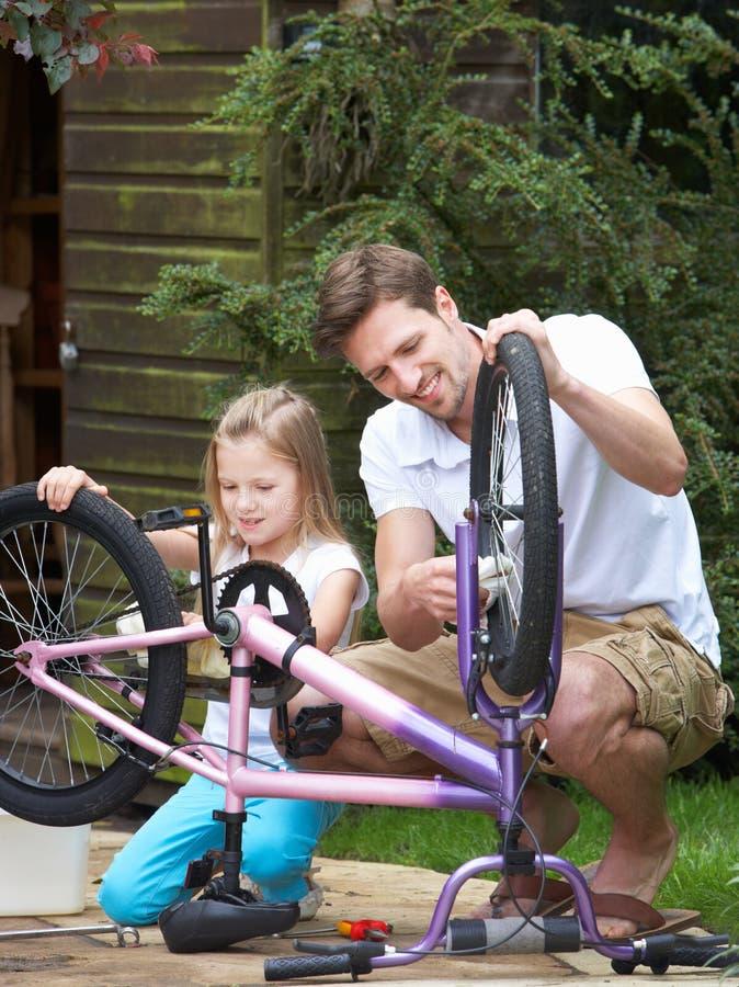 FaderAnd Daughter Cleaning cykel tillsammans royaltyfria bilder