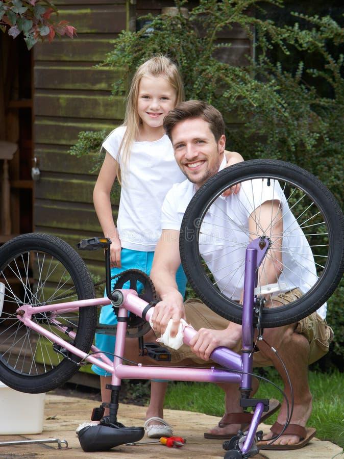 FaderAnd Daughter Cleaning cykel tillsammans royaltyfri bild