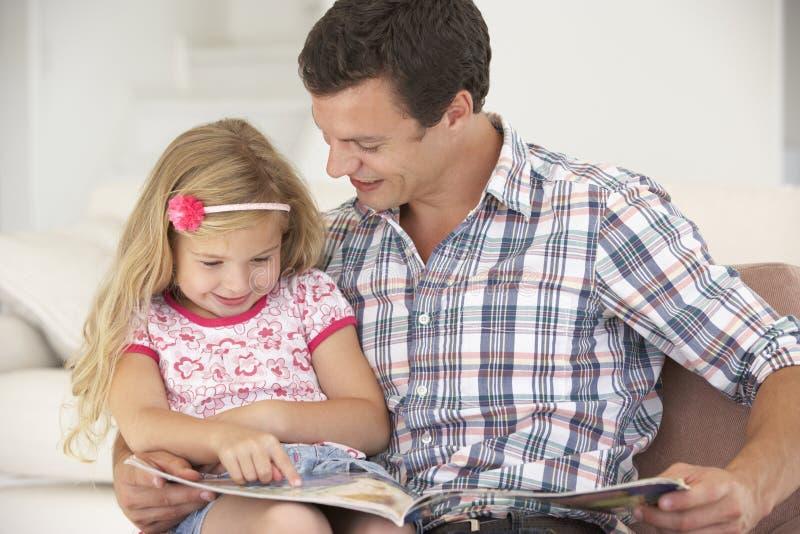 FaderAnd Daughter Reading bok hemma royaltyfria bilder