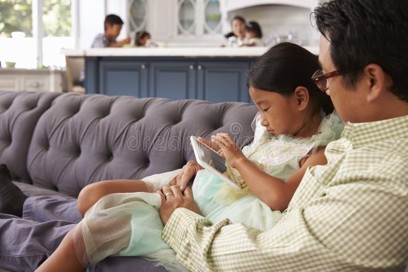 FaderAnd Daughter Sit On Sofa Using Digital minnestavla hemma royaltyfria foton