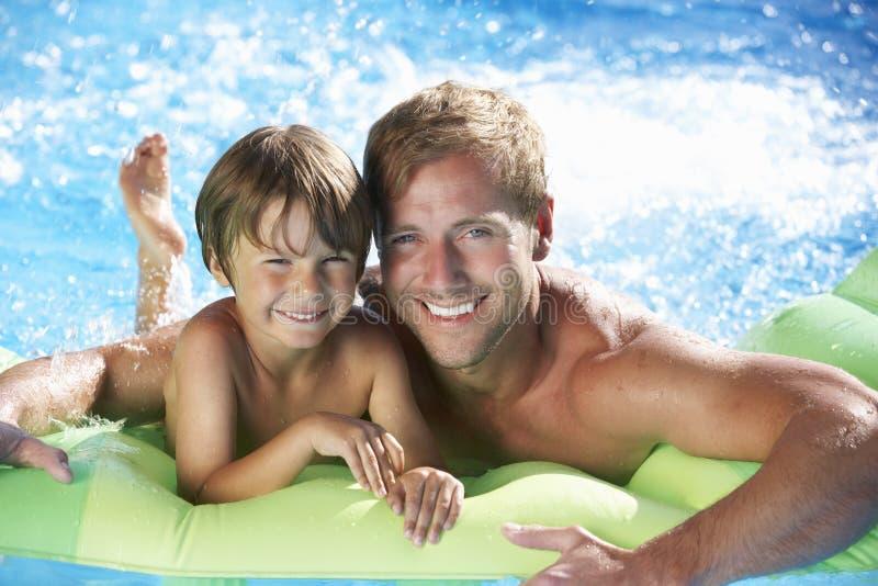 FaderAnd Son On ferie i simbassäng royaltyfri foto