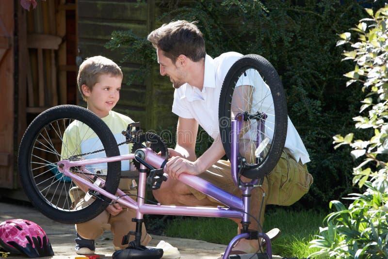 FaderAnd Son Mending cykel tillsammans royaltyfri fotografi