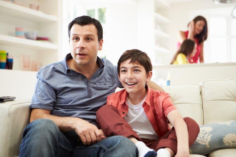 FaderAnd Son Watching sportar på TV arkivbilder