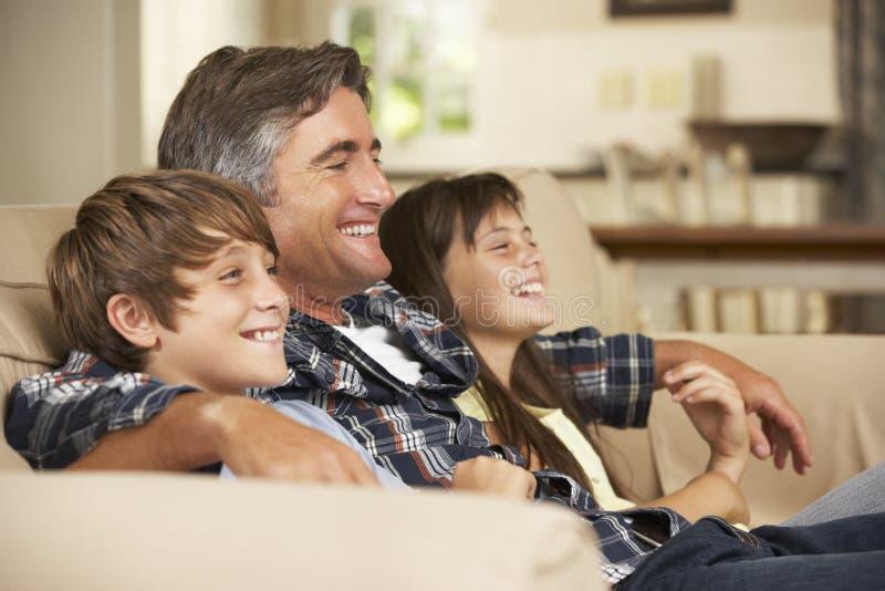 FaderAnd Two Children sammanträde på Sofa At Home Watching TV tillsammans arkivfoto
