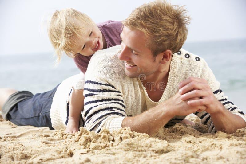 FaderAnd Young Daughter sammanträde på stranden tillsammans royaltyfri foto