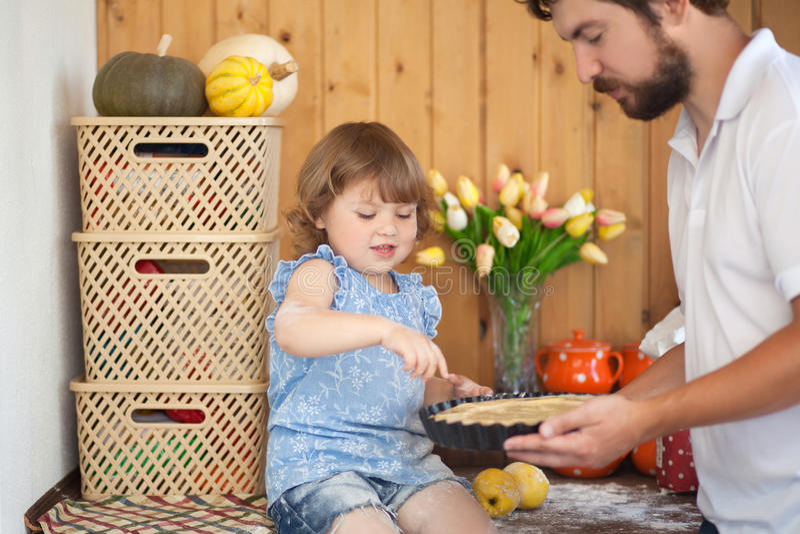 Faderbakningkaka med hans gulliga lilla dotter arkivbilder