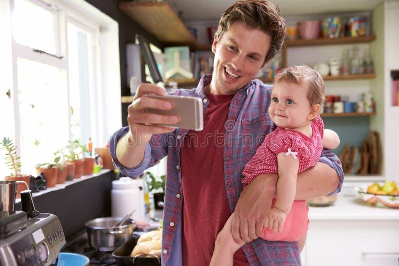 FaderCooks Meal Whilst hållande ung dotter royaltyfri fotografi