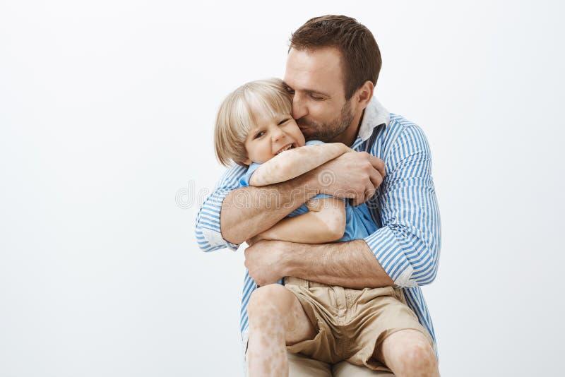 Faderförälskelser hans lilla son gillar inget annan Gulligt snyggt att bry sig krama för farsa och kyssande barn i kinden som kän royaltyfri foto
