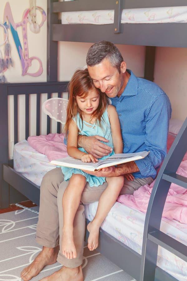 Faderfarsa och hemmastadd läsebok för dotterflicka arkivfoto