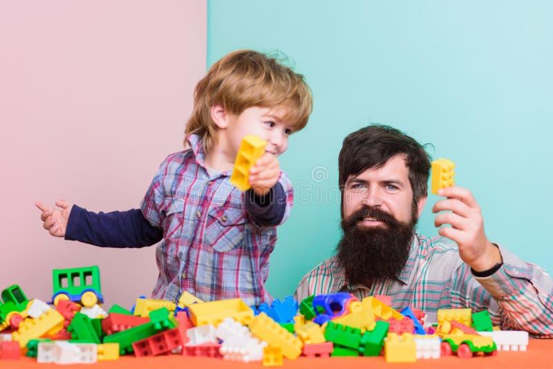 fadergyckel har sonen Sk?ggig hipster- och pojkelek tillsammans Farsa och barn att bygga plast- kvarter Betydelse av royaltyfria foton