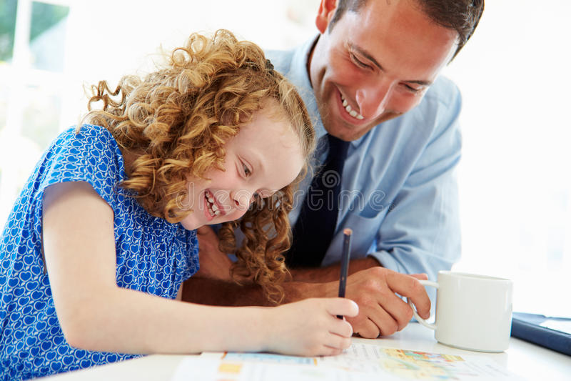 FaderHelping Daughter With läxa i kök arkivfoton