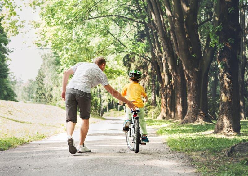 Faderhjälp hans sonritt en cykel arkivfoton