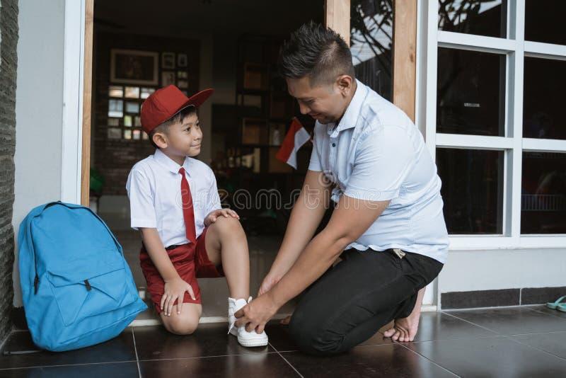 Faderhjälp hennes son som får skolmogen i morgonen royaltyfri bild