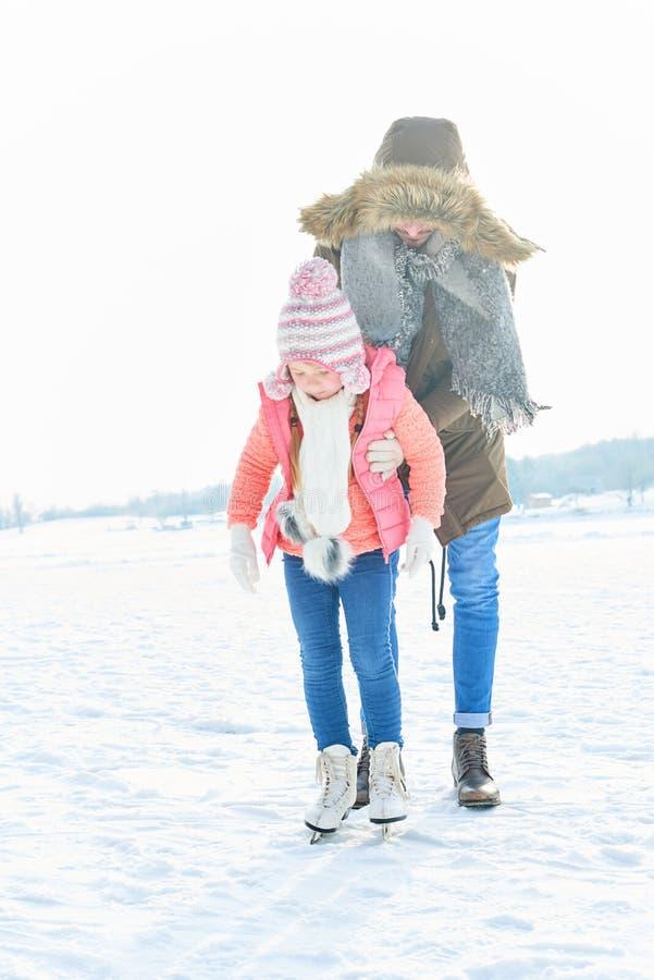 Faderhjälpdottern åker skridsko arkivfoto