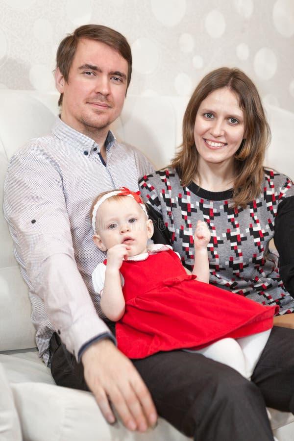 Faderinnehavet behandla som ett barn flickan, medan sitta med barnmodern på soffan arkivbilder