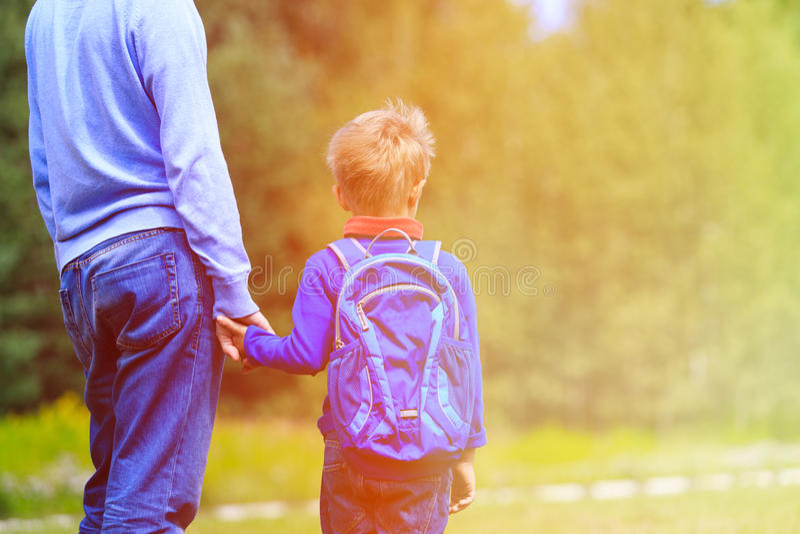 Faderinnehavhand av den lilla sonen med ryggsäcken fotografering för bildbyråer