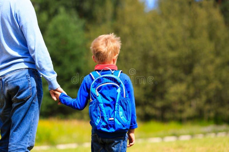 Faderinnehavhand av den lilla sonen med ryggsäcken arkivbild