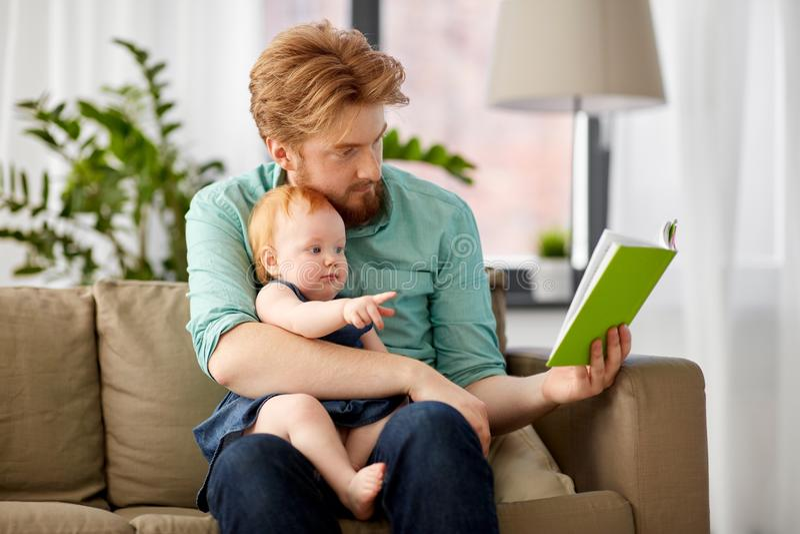 Faderläseboken för behandla som ett barn dottern hemma royaltyfri foto