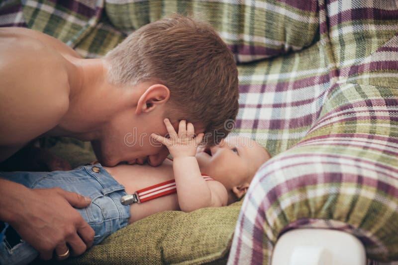 Faderlek med behandla som ett barn sonen p? soffan arkivbilder
