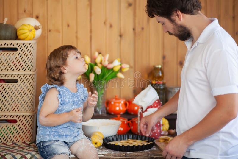 Fadermatlagningkaka med hans gulliga lilla dotter royaltyfri bild