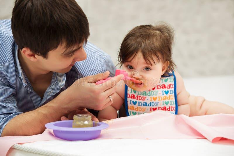 Fadermatning behandla som ett barn flickan på filten hemma royaltyfri fotografi