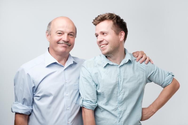 fadern är stolt av hans mogna son Han rymmer hans skuldra som är lycklig att ha ett sådant stort barn royaltyfria bilder