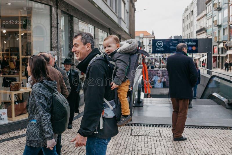 Fadern bär hans son i en special ryggsäck och ler arkivfoton
