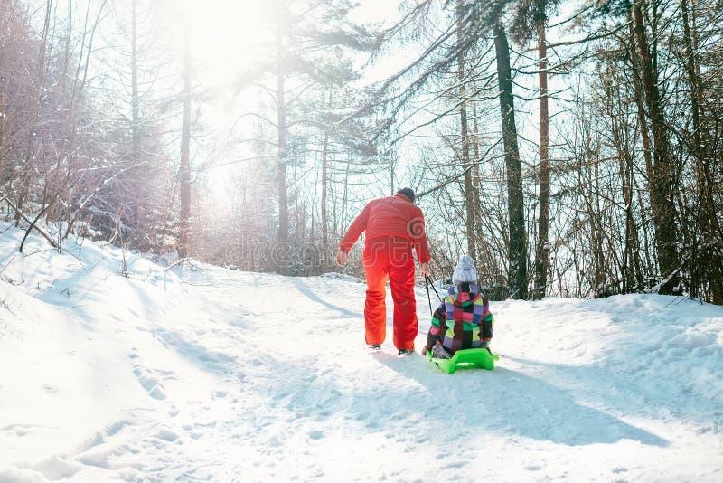 Fadern bär släden med hans lilla dotter på snösloen royaltyfri foto