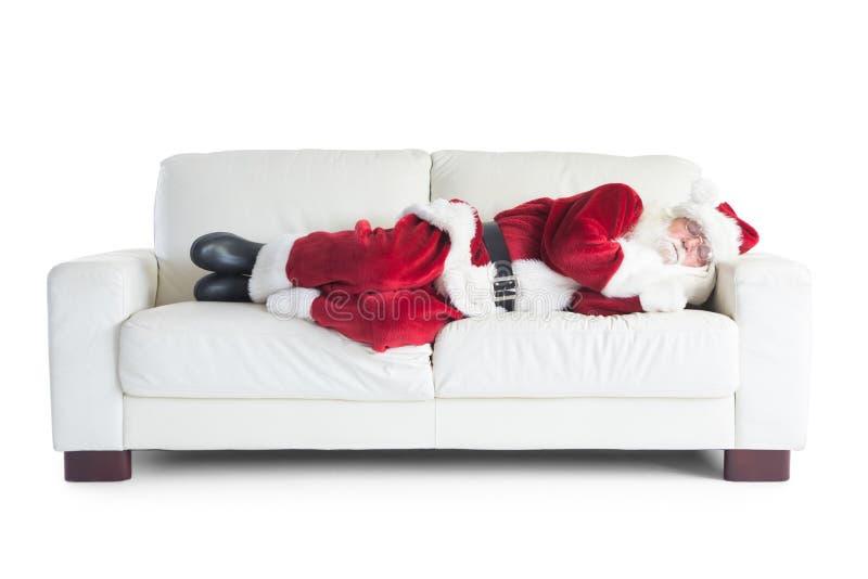 Fadern Christmas sover på en soffa royaltyfri fotografi