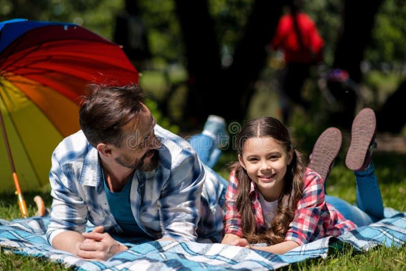 Fadern And Daughter Are som ligger på filten i, parkerar familj som har picknicken Färgrikt paraply på bakgrunden arkivbild