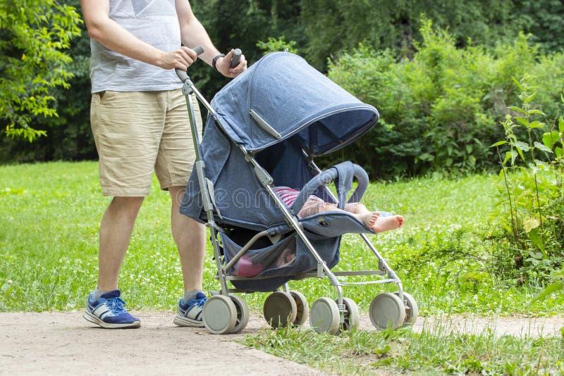 Fadern går med barnet parkerar in Ung man med den blåa sittvagnen, enda ben för främre sikt Att bry sig farsan med sommarbyxa och arkivbilder