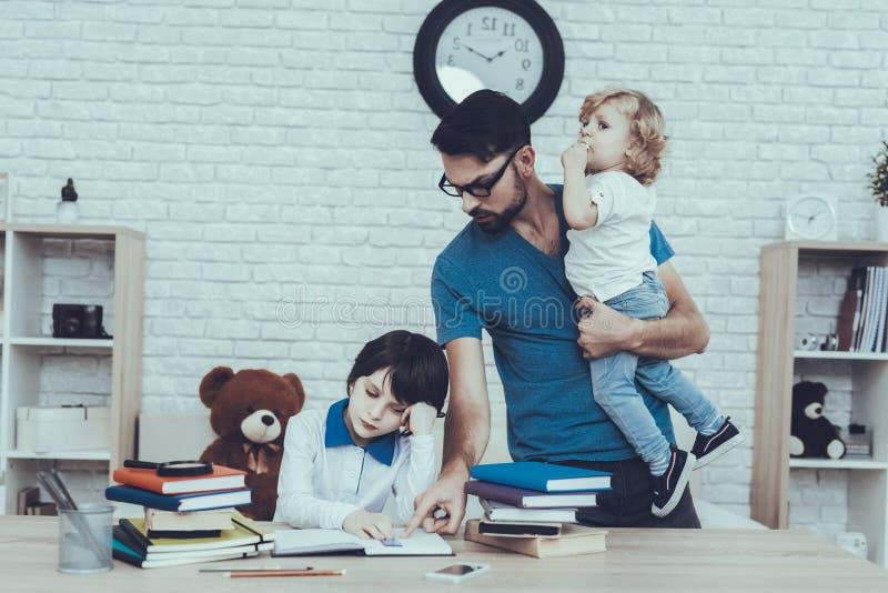 Fadern gör en läxa med sonen royaltyfri fotografi