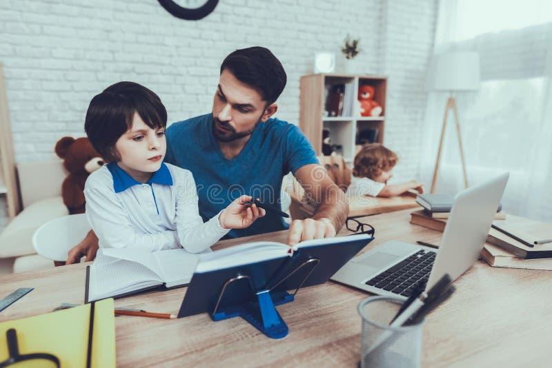 Fadern gör en läxa med sonen royaltyfria foton