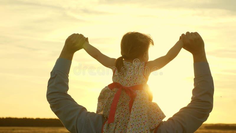 Fadern g?r med hans dotter p? hans skuldror i str?lar av solnedg?ngen Farsan b?r p? skuldror av hans ?lskade barn royaltyfria foton