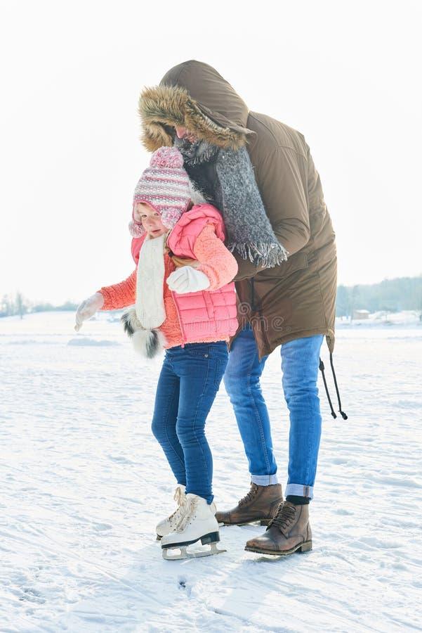 Fadern hjälper barnet med att åka skridsko royaltyfria foton