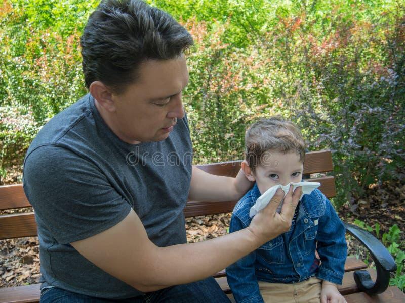 Fadern hjälper hans son att blåsa hans näsa arkivfoton