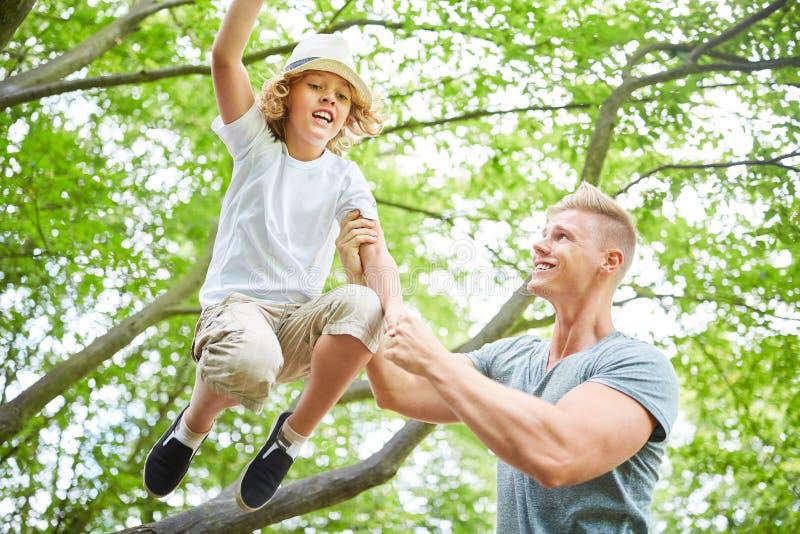 Fadern hjälper hans son att klättra arkivbild