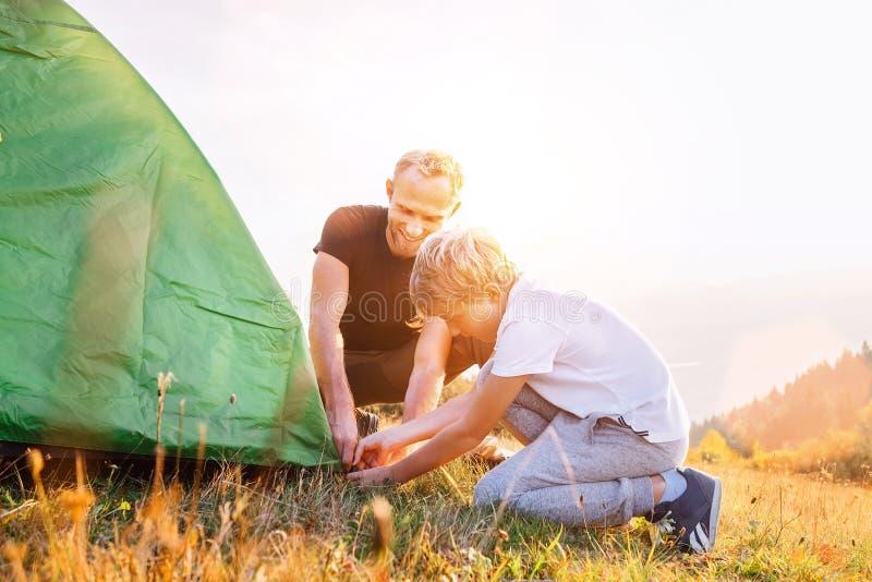 Fadern hjälper hans soninställningstält på solnedgångskoggläntan fotografering för bildbyråer