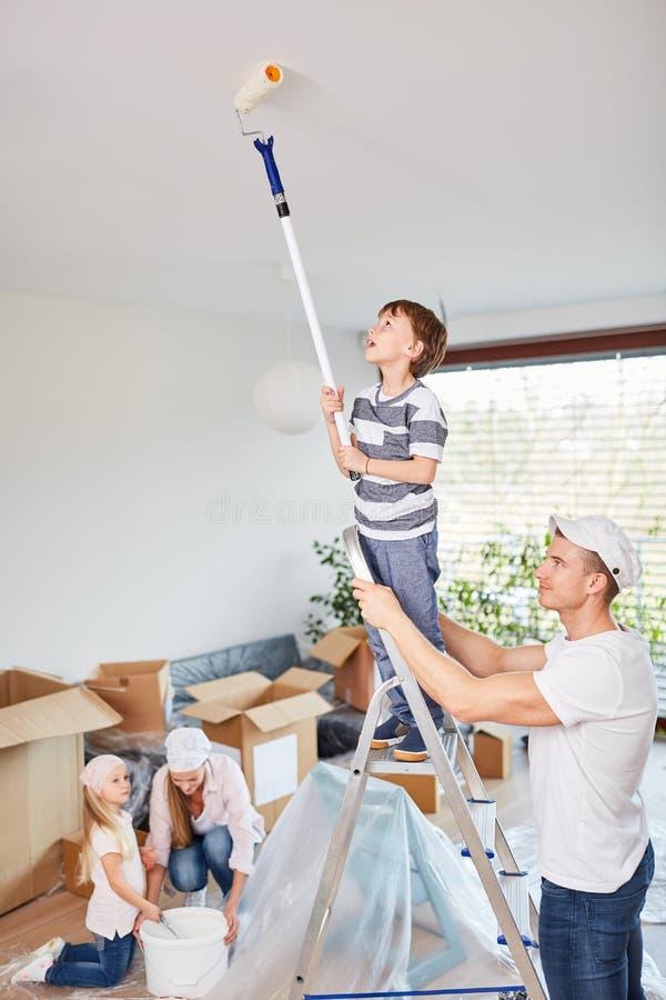 Fadern hjälper sonen på stegen, medan slå royaltyfri bild