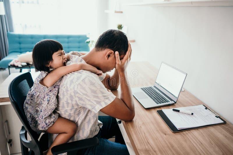 Fadern känner stressade mellanjobb av dottern, medan arbeta royaltyfria foton