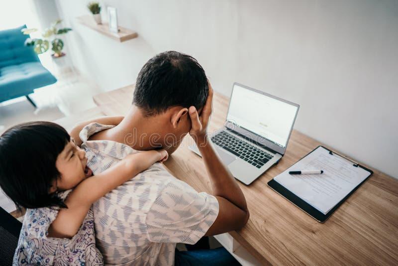 Fadern känner stressade mellanjobb av dottern, medan arbeta royaltyfri fotografi