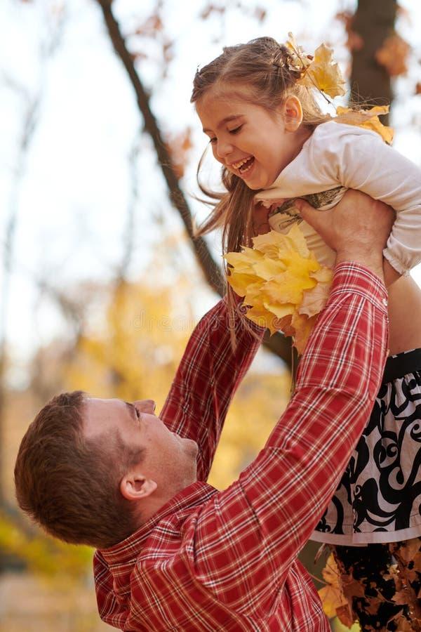 Fadern kastar dottern som är hög upp i höststad, parkerar Dem som poserar, le som spelar Ljusa gula träd royaltyfri foto