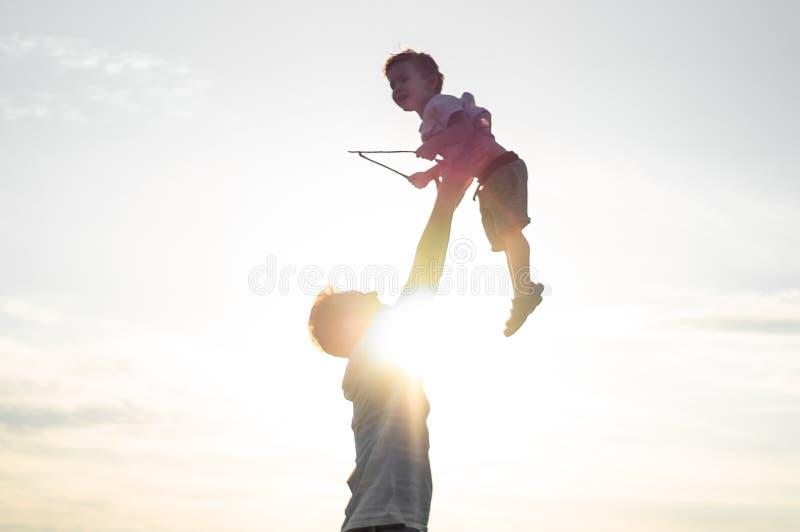 Fadern kastar upp hans gulliga och lilla son i den nya luften Avla dagen för ` s, behandla som ett barn fadern och hans son pojke royaltyfri fotografi