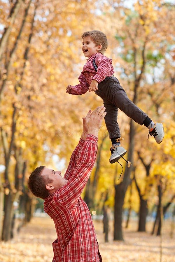 Fadern kastar upp pojkehöjdpunkten Fadern och sonen spelar, och ha gyckel i höststad parkera Dem som poserar, le som spelar Brigh royaltyfria foton
