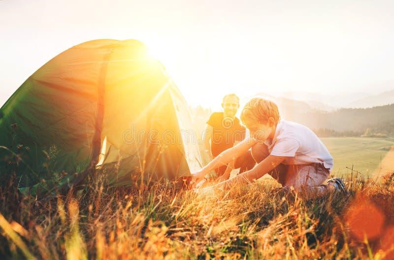 Fadern lär hans campa tält för sonaktiveringen på solnedgångskoggläntan royaltyfria foton