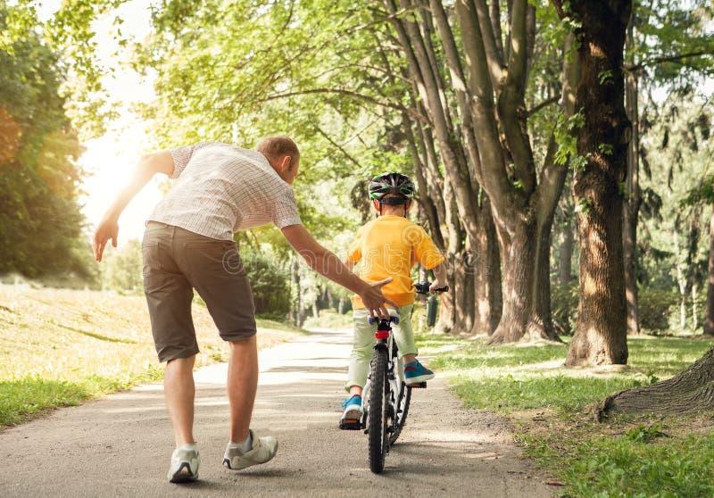 Fadern lär hans lilla son för att rida en cykel royaltyfri bild